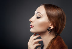 Beautiful young redhead woman isolated on dark background royalty free stock photography