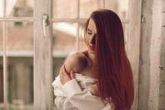 Beautiful young redhead woman with long hair sitting on windowsil royalty free stock images
