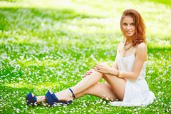 Beautiful young redhead woman on meadow with white flowers. On warm summer day Stock Photography
