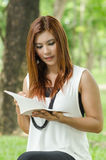 Beautiful young redhead woman reading a book. Beautiful young redhead Asian woman reading a book while standing outdoors in a park concentrating with a serious Royalty Free Stock Image