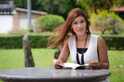 Beautiful young redhead woman reading outdoors. A beautiful young redhead woman reading outdoors standing sideways to the camera with a book in her hands Royalty Free Stock Photo