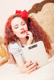 Beautiful young redhead woman reading with tablet Stock Images