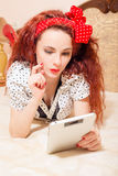 Beautiful young redhead woman reading with tablet Royalty Free Stock Image