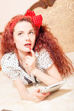 Beautiful young redhead woman reading with tablet Royalty Free Stock Images