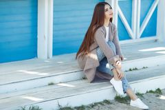 Beautiful woman in spring rests by the sea. A beautiful young redhead woman is standing indoors next to a white wall stock photo