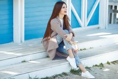 Beautiful woman in spring rests by the sea. A beautiful young redhead woman is standing indoors next to a white wall royalty free stock images