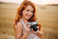 Beautiful young redhead woman with vintage camera Royalty Free Stock Images