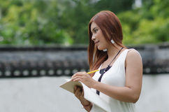 Beautiful young redhead woman writing in a noteboo Royalty Free Stock Photo