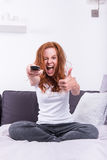 Beautiful, young, redheaded woman likes the TV program.  Royalty Free Stock Images