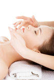 Beautiful young relaxed woman enjoy receiving face massage. At spa saloon Stock Photos