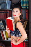 Beautiful young retro pinup woman reading book in the library. Stock Photo