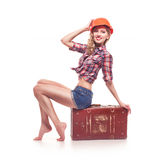 Young pinup woman with suitcase on white. Beautiful young retro pinup woman with suitcase on white background royalty free stock image