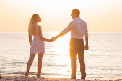 Beautiful young romantic couple holding hands on seaside in rays. Beautiful young romantic couple  holding hands on seaside in rays of rising sun. Two happy Royalty Free Stock Images