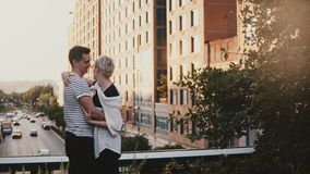 Beautiful young romantic couple standing and hugging on an amazing New York sunset bridge, urban buildings background. stock video
