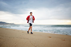 Beautiful young runner in sports red windbreaker runs along the beach on beautiful sea background. Morning jogging, fitnes and healthily lifestyle, sport and stock photography