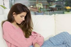 Sad lonely woman at home in winter pensive heart broken Royalty Free Stock Image