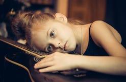 Beautiful young sad girl hug a guitar Stock Photo