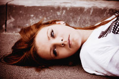 Beautiful young sad girl lying on asphalt Royalty Free Stock Photos