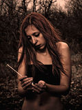 Beautiful young sad girl with match in hands. Portrait of a beautiful young sad girl with match in hands Royalty Free Stock Photos