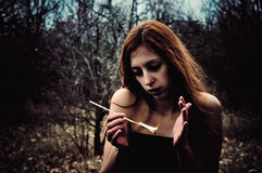 Beautiful young sad girl with match in hands. Portrait of a beautiful young sad girl with match in hands Stock Image