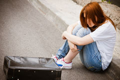 Beautiful young sad girl sitting on asphalt Royalty Free Stock Image
