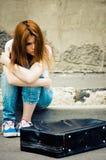 Beautiful young sad girl sitting on asphalt Stock Image