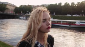 Beautiful young sad girl walking along waterfront at sunset stock video footage