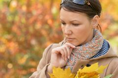 Portrait of beautiful young sad woman in autumnal park stock photo