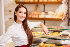 Beautiful young saleswoman in a bakery Royalty Free Stock Images