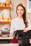 Beautiful young saleswoman in a bakery Stock Images
