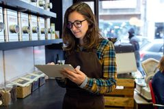 Beautiful young saleswoman doing inventory in a retail store selling coffee. Portrait of beautiful young saleswoman doing inventory in a retail store selling stock photo