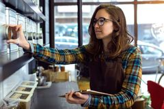 Beautiful young saleswoman doing inventory in a retail store selling coffee. Portrait of beautiful young saleswoman doing inventory in a retail store selling stock photography