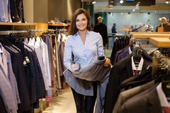 Beautiful young saleswoman helps the customer to choose a jacket in suit shop. stock photos
