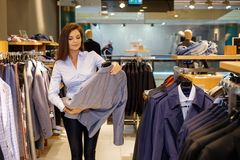 Beautiful young saleswoman helps the customer to choose a jacket in suit shop. stock image
