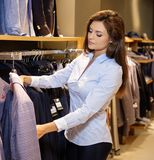 Beautiful young saleswoman helps the customer to choose a jacket in suit  shop. Stock Images