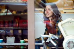 Beautiful young saleswoman relaxing and drinking coffee in organic shop. Royalty Free Stock Photography