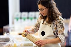 Beautiful young saleswoman taking pasta from a shopping bag in an organic store. Stock Photography