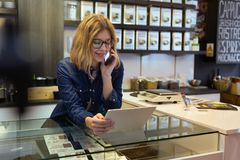 Beautiful young saleswoman using her digital tablet in organic shop. Royalty Free Stock Images