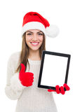 Beautiful young Santa girl showing tablet and thumb up Royalty Free Stock Photos