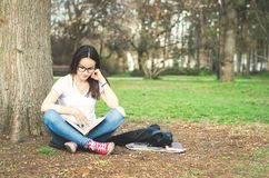 Beautiful young school or college girl with long hair and eye glasses sitting on the ground in the park reading the books and stud. Y for exam Royalty Free Stock Image