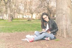 Beautiful young school or college girl with long hair, eyeglasses and black leather jacket sitting on the ground in the park readi royalty free stock photo