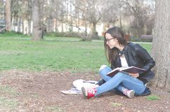Beautiful young school or college girl with long hair, eyeglasses and black leather jacket sitting on the ground in the park readi royalty free stock images