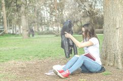 Beautiful young school or college girl with long hair, eyeglasses and black leather jacket sitting on the ground in the park readi royalty free stock image