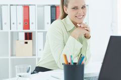 Beautiful young secretary  holding her head in her arms sitting at office. Royalty Free Stock Image