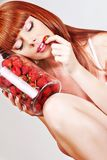 Beautiful young red hair woman with strawberries. Beautiful young sensible red-hair, blue eyes woman wearing pink underwear strawberries eating them from the can stock photography