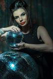Beautiful young sensual woman holding disco ball Royalty Free Stock Images