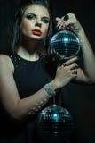 Beautiful young sensual woman holding disco ball Royalty Free Stock Photo