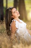 Beautiful young serene woman sitting in a meadow Royalty Free Stock Photos