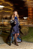 Beautiful young sexy blonde wearing evening makeup in elegant fitting dress fashionable stylish expensive fur coat walk night stre Stock Images