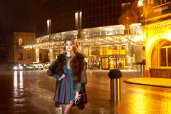 Beautiful young sexy blonde wearing evening makeup in elegant fitting dress fashionable stylish expensive fur coat walk night stre Stock Image